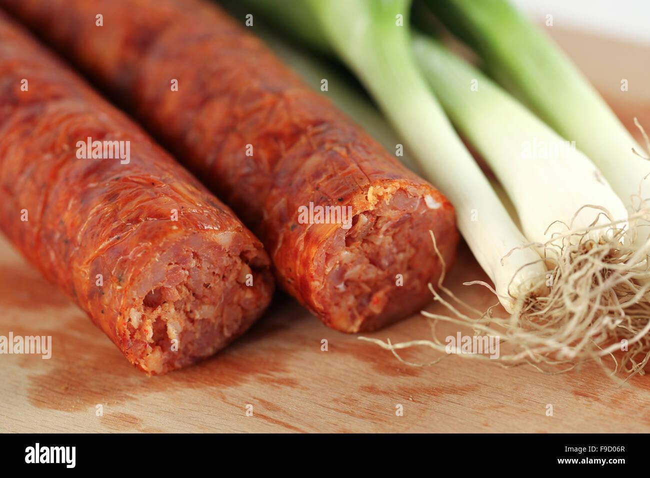 Délicieux saucisson de porc avec l'oignon sur plaque de bois Photo Stock