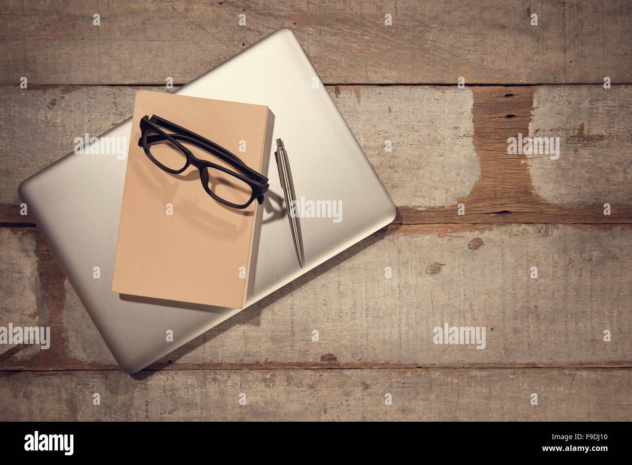 Bureau avec ordinateur portable livre journal stylo et lunettes