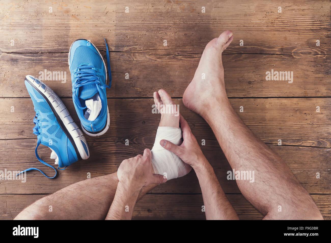 Blessé méconnaissable runner assis sur un plancher en bois historique Photo Stock
