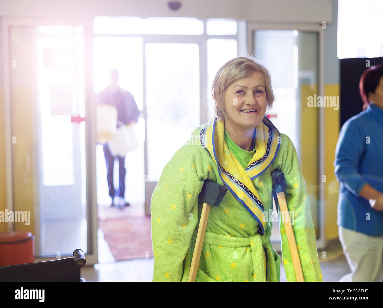 Senior woman walking blessé par couloir de l'hôpital avec des béquilles Photo Stock