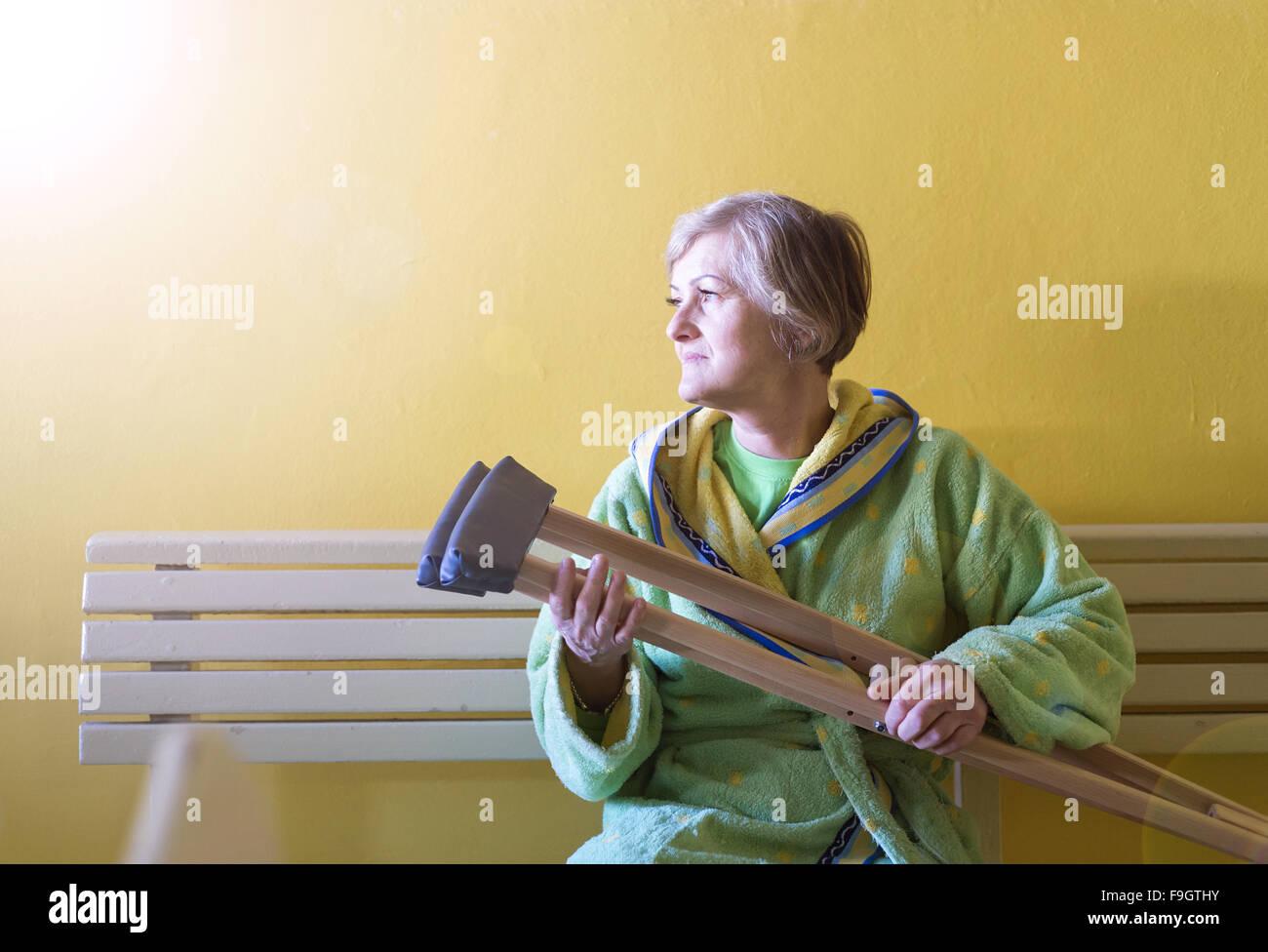 Senior woman blessés assis dans le couloir de l'hôpital holding béquilles Photo Stock