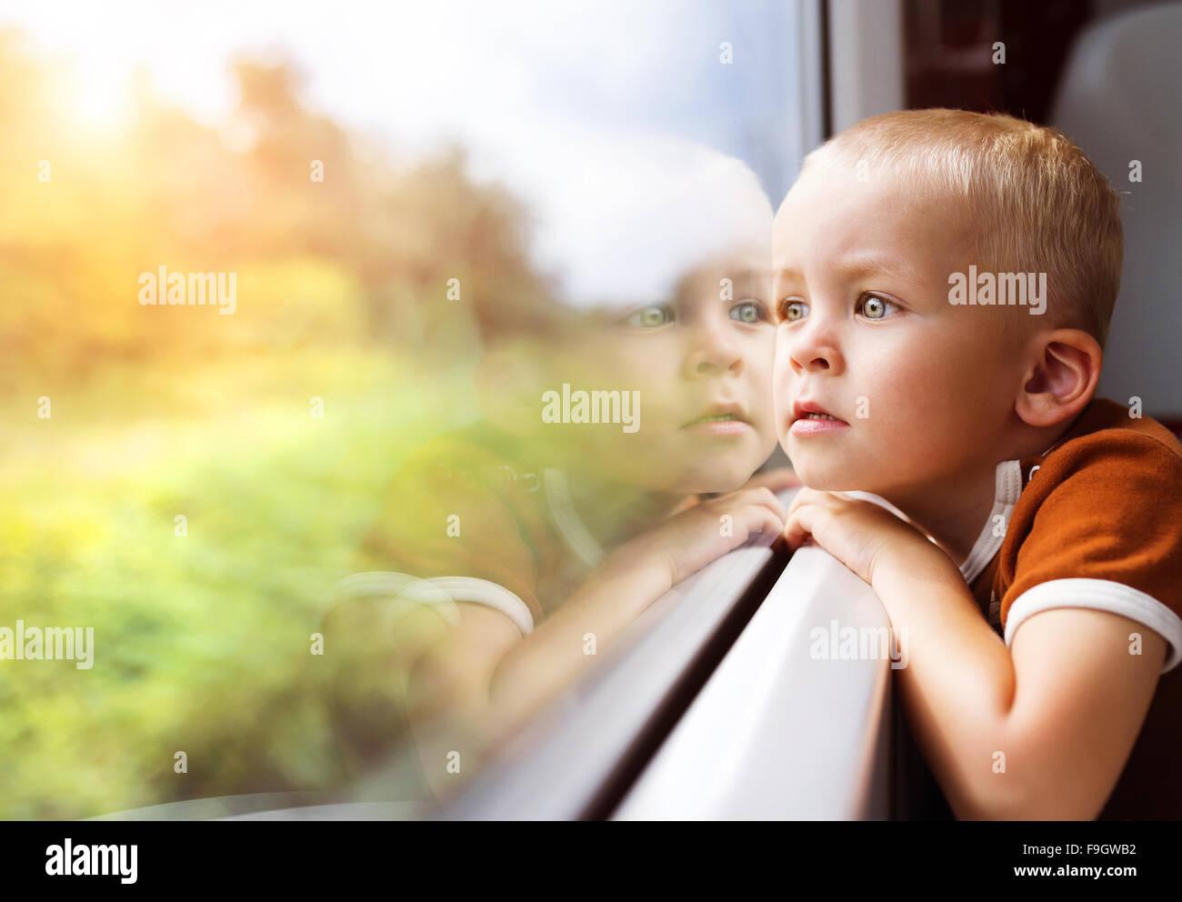 Petit garçon voyageant en train à l'extérieur de la fenêtre. Photo Stock