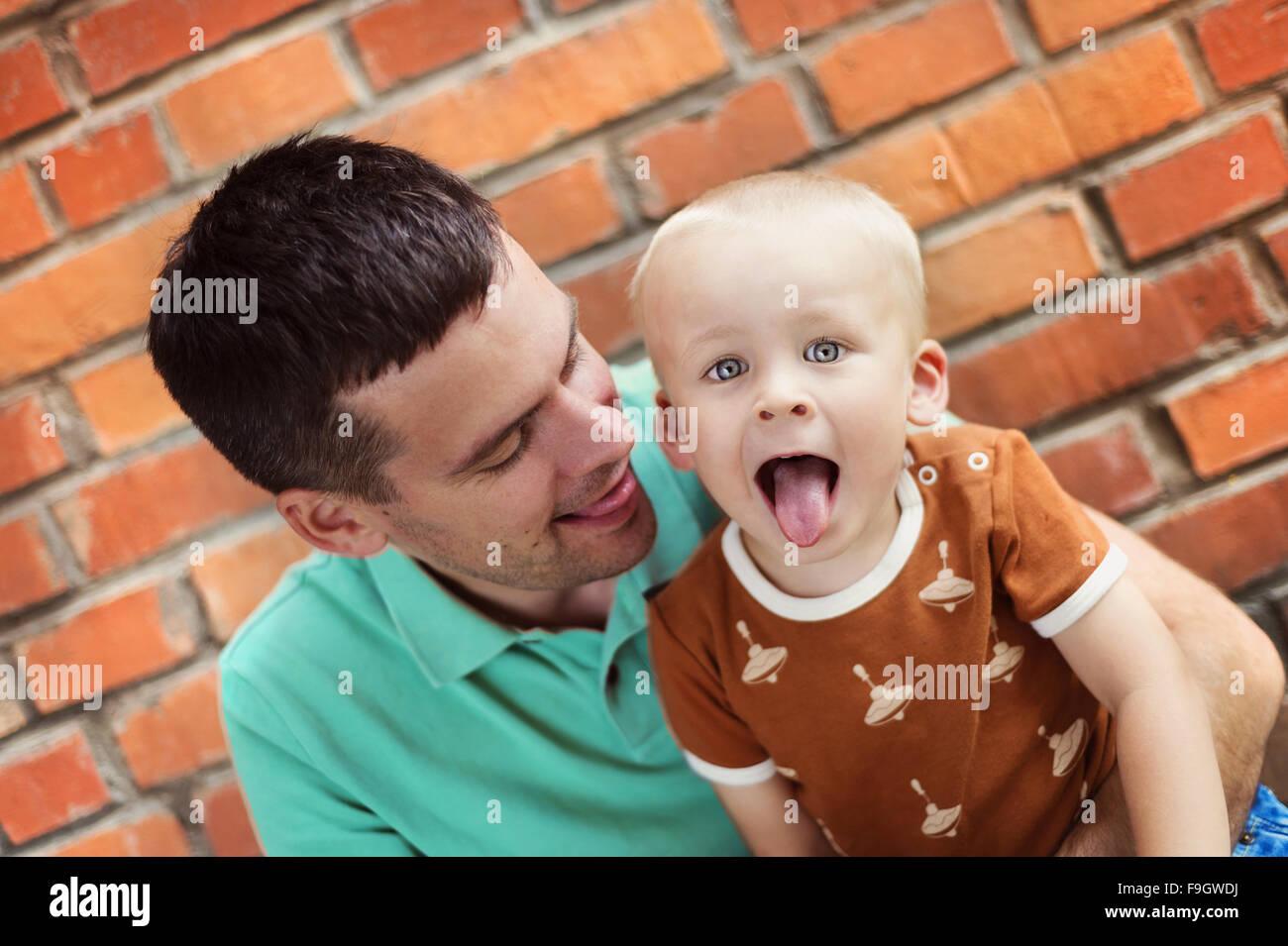 Père et fils faire des grimaces ensemble sur un mur de briques historique Banque D'Images