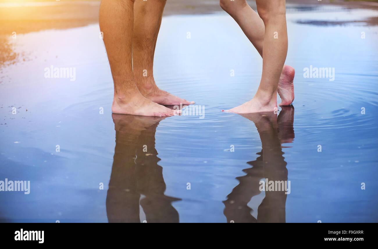 Méconnaissable la femme et l'homme debout pieds nus dans une flaque Photo Stock