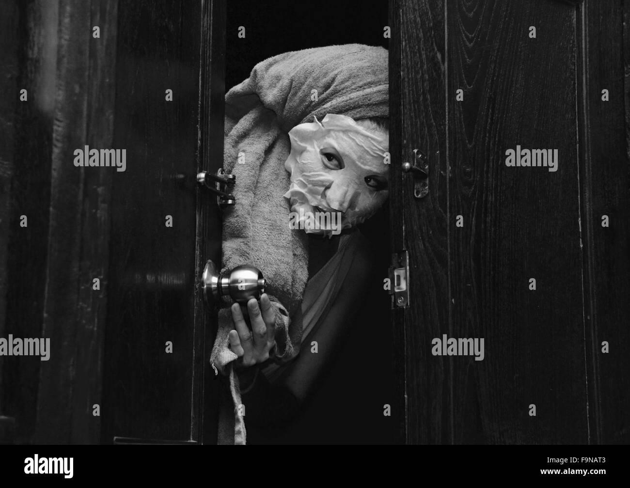 À la femme japonaise a jeté une porte portant un masque de nettoyage Photo Stock