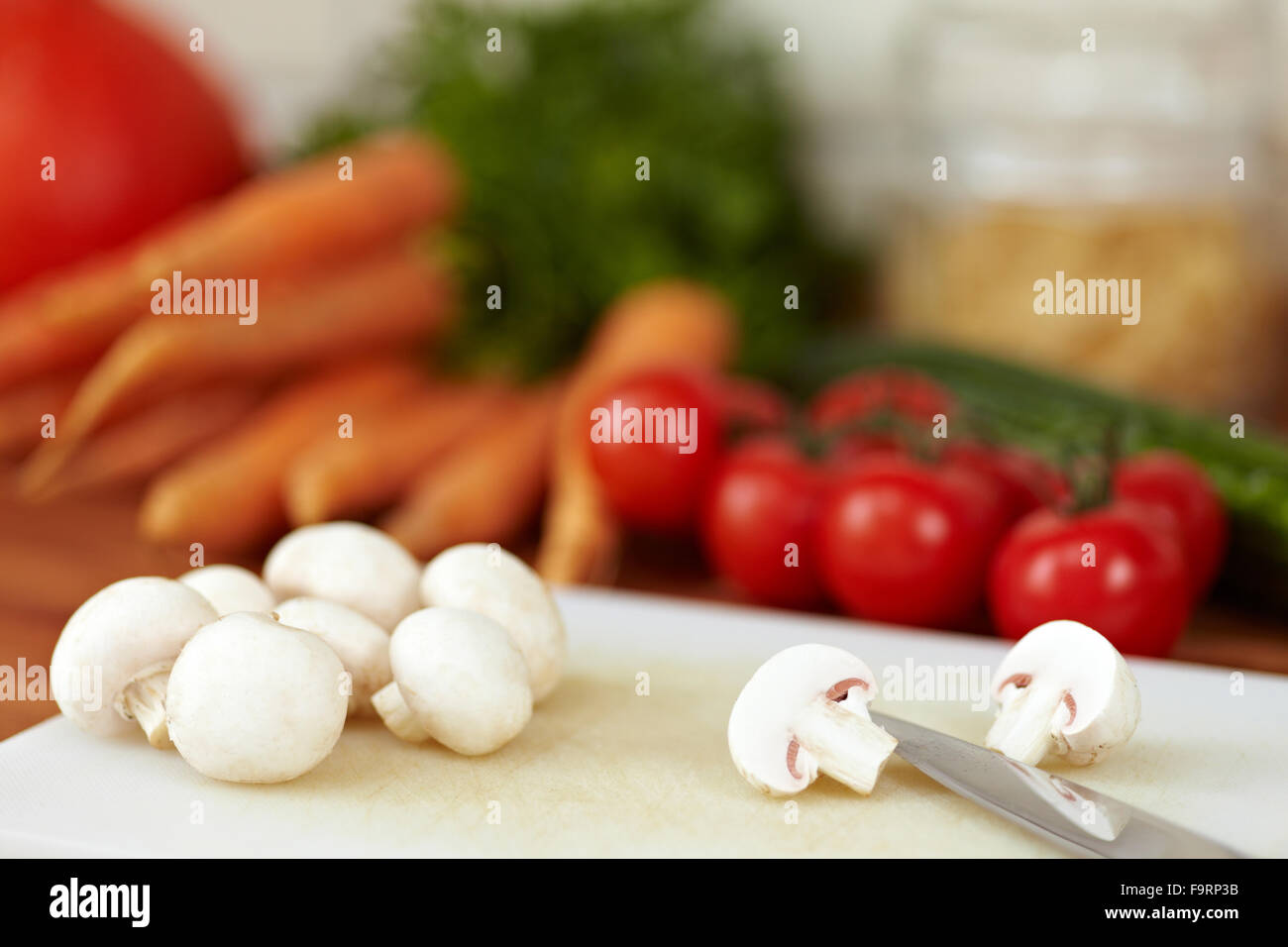 Champignons blancs cultivés de coupe en deux avec un couteau Photo Stock