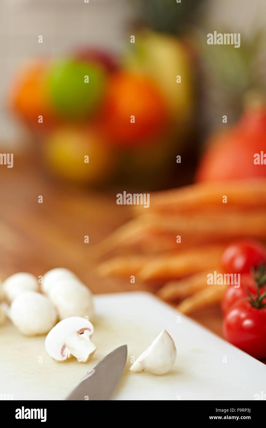 Couteau sur un comptoir de cuisine champignons blancs de coupe en deux Photo Stock