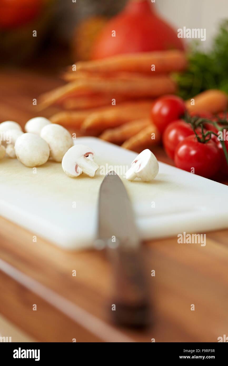 La pointe du couteau sur une planche à découper avec champignons de Paris Photo Stock