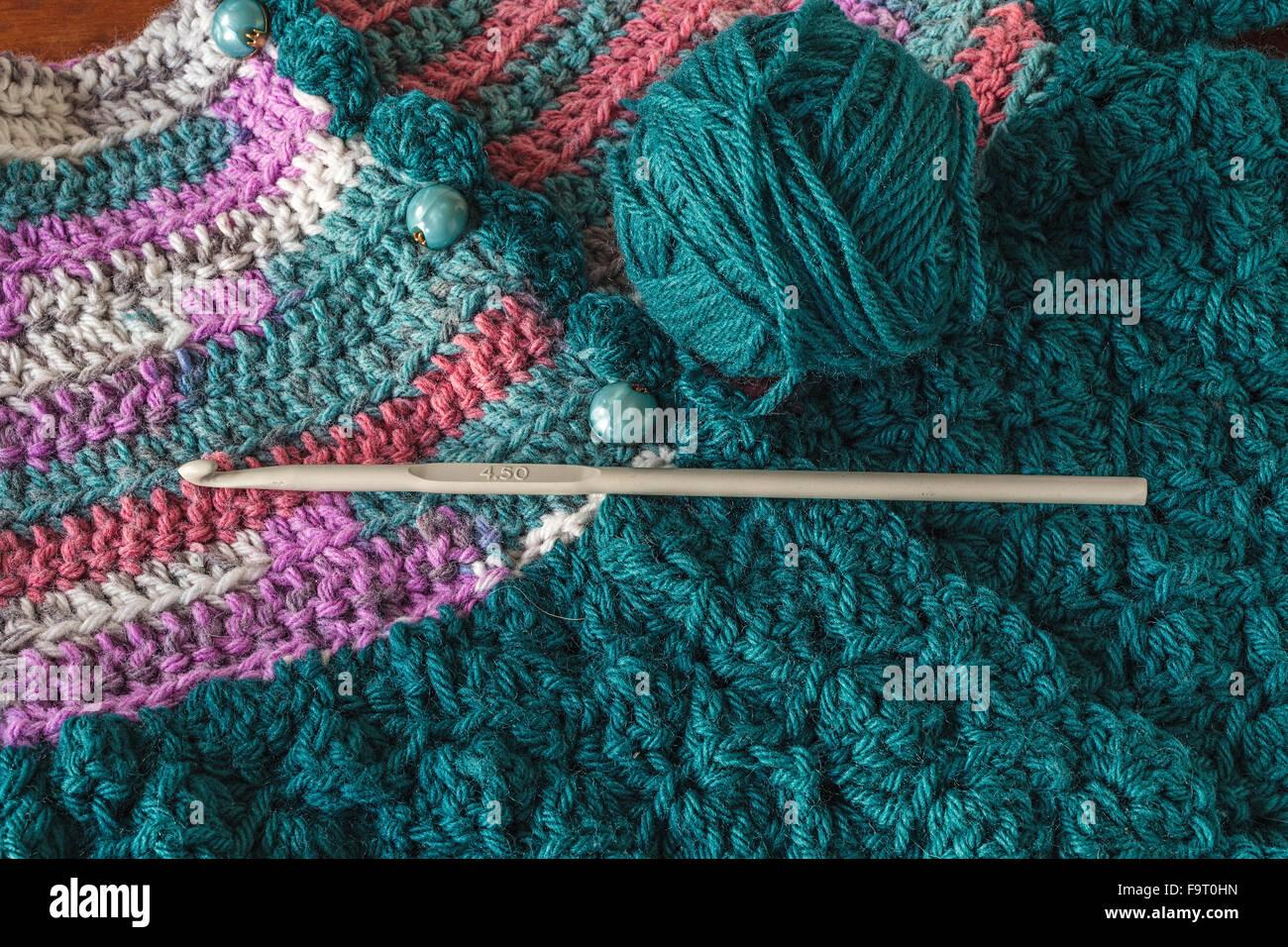 Pull bébé en crochet avec un crochet et pelote de laine. Photo Stock