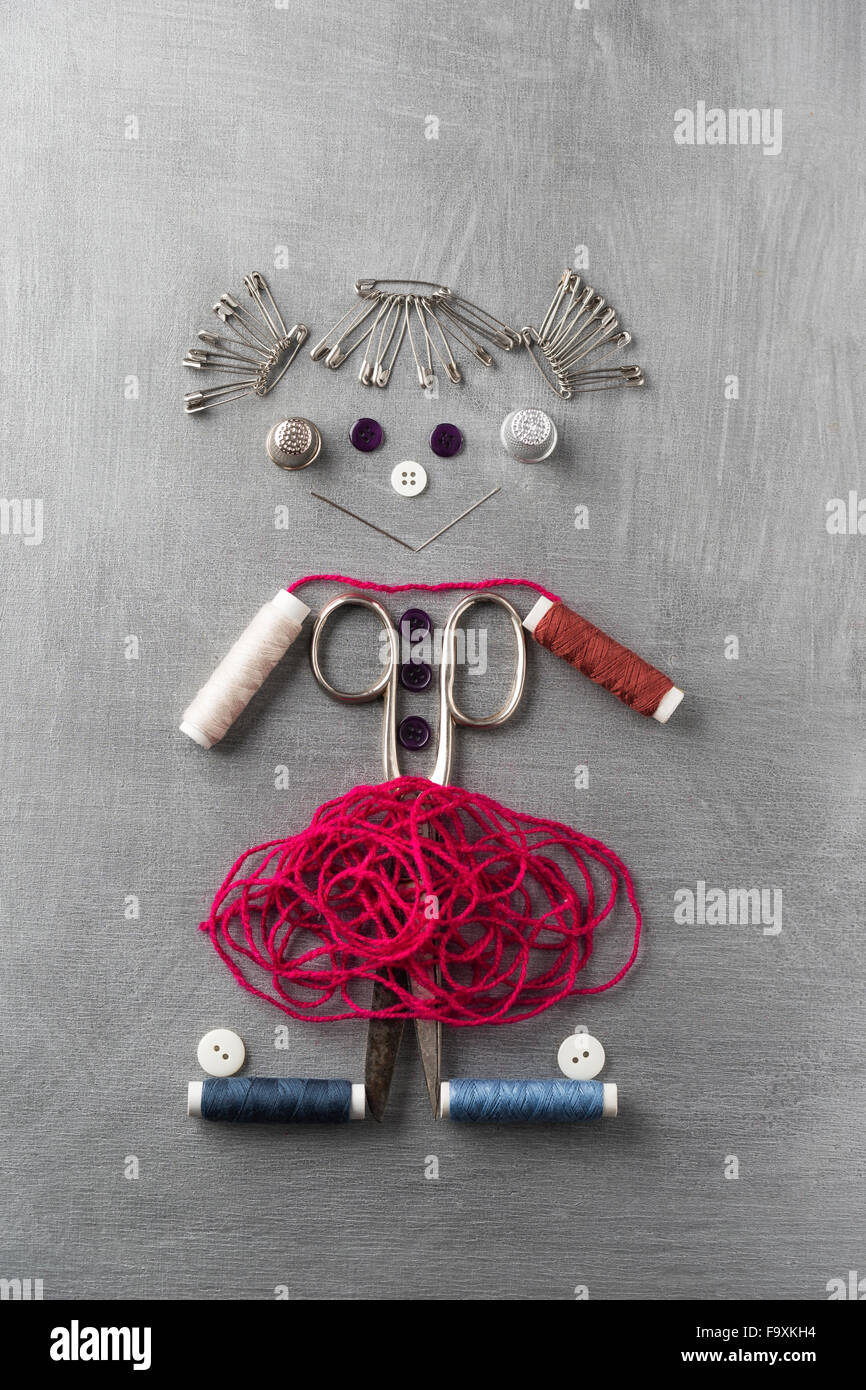 Articles de couture de bâtiment figure une jeune fille souriante sur fond gris Photo Stock