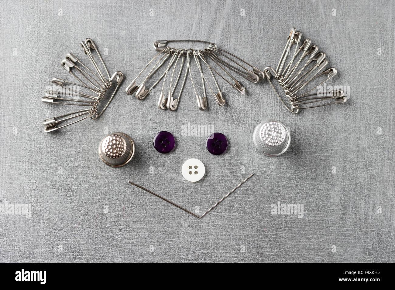 Visage souriant d'une jeune fille construit des points de couture sur fond gris Photo Stock