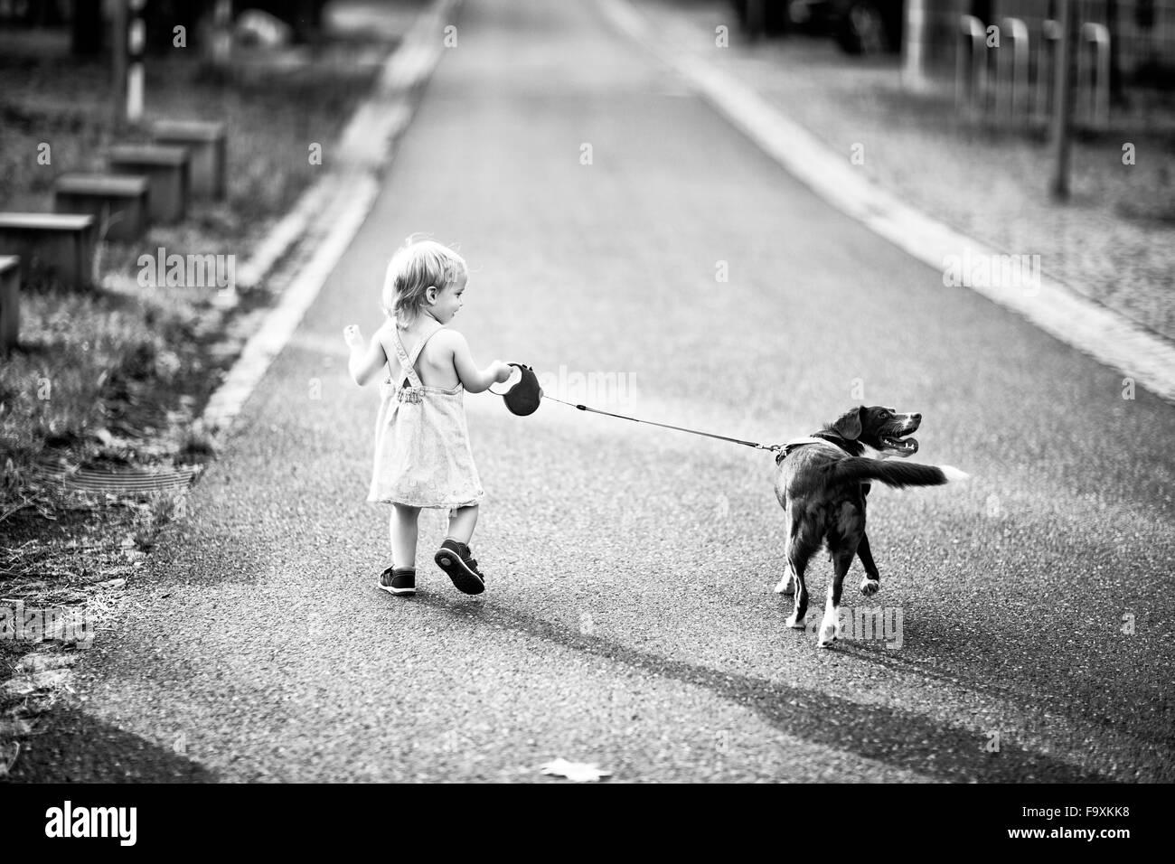 Vue de l'arrière petite fille qui marche le long de la rue avec son chien Photo Stock
