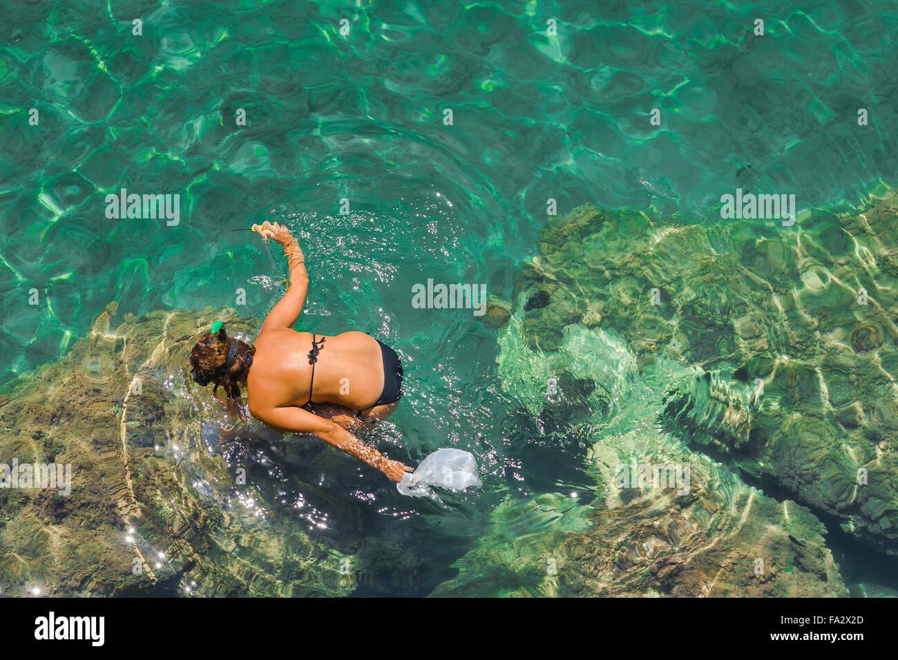 Rock femme intérieure, une femme en bikini les recherches des moules au milieu des rochers sur l'île Photo Stock