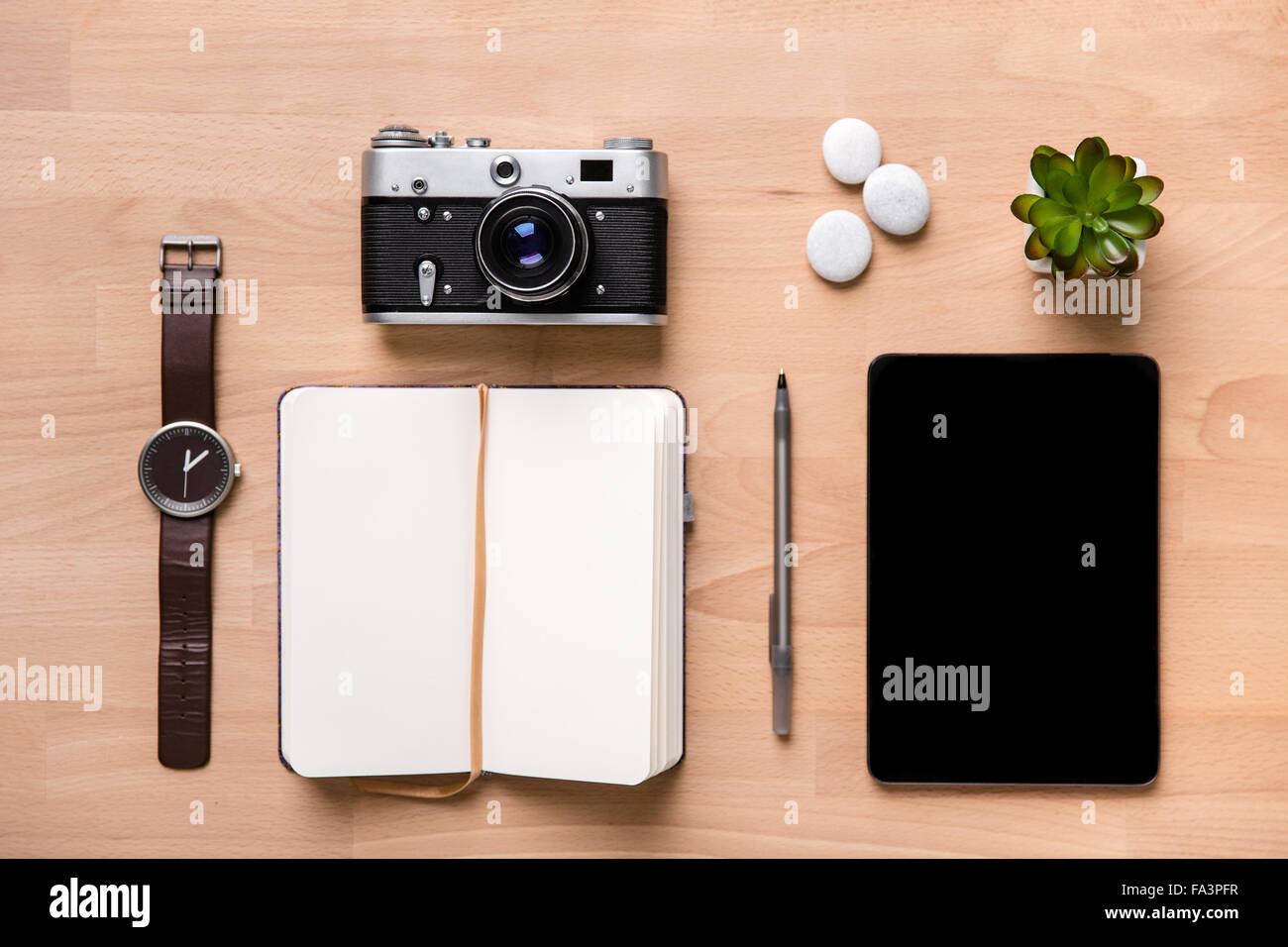 Vue de dessus ouvert blank notepad, stylo, montre, vintage camera, tablette et fleur sur fond de bois Photo Stock