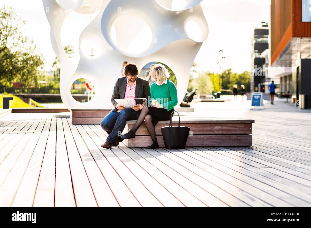 Toute la longueur du businessman with female colleague discuter à Malmo vivre Photo Stock