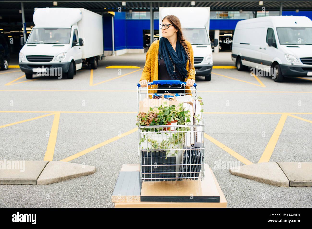 Jeune femme en poussant le chariot plein d'achats dans le parc automobile Photo Stock