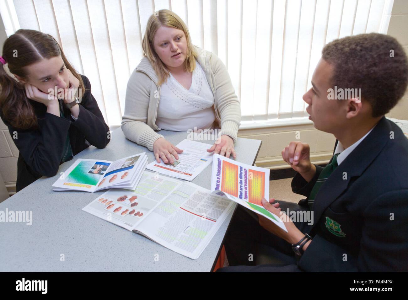 Enseignant au secondaire en discussion avec des étudiants pendant un cours de biologie, Photo Stock