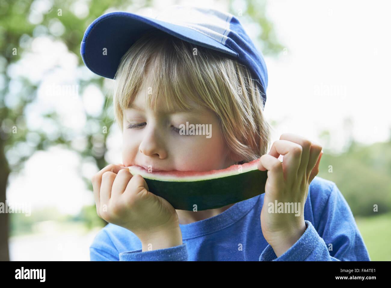 Garçon profitant tranche de pastèque au picnic, Munich, Bavière, Allemagne Photo Stock