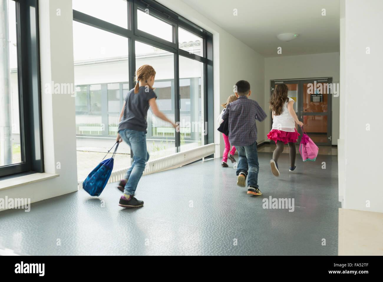Les enfants courir avec des sacs de sport dans couloir de sports hall, Munich, Bavière, Allemagne Photo Stock