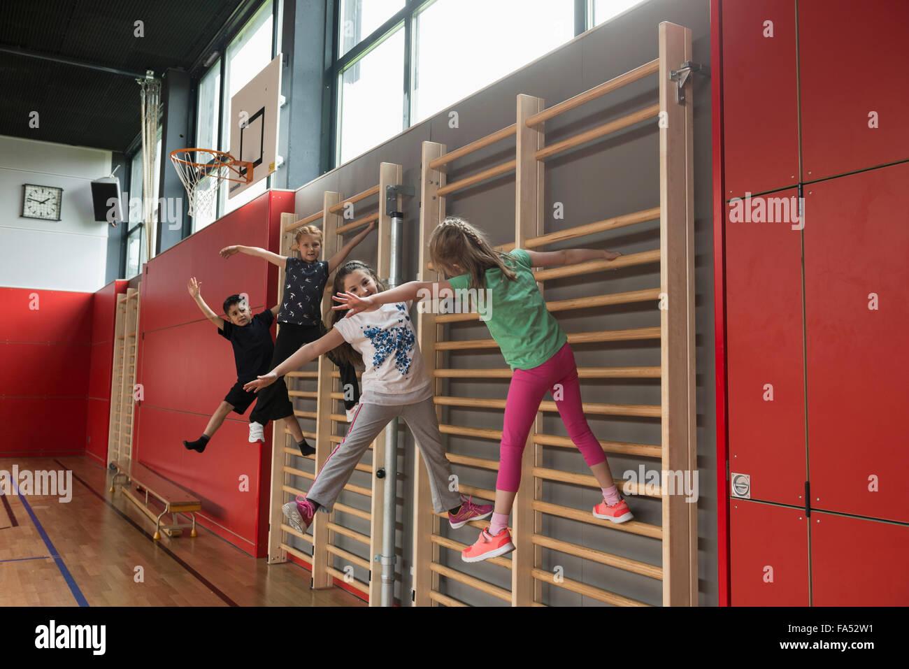 Quatre enfants exerçant sur le mur de bars dans sports hall, Munich, Bavière, Allemagne Photo Stock