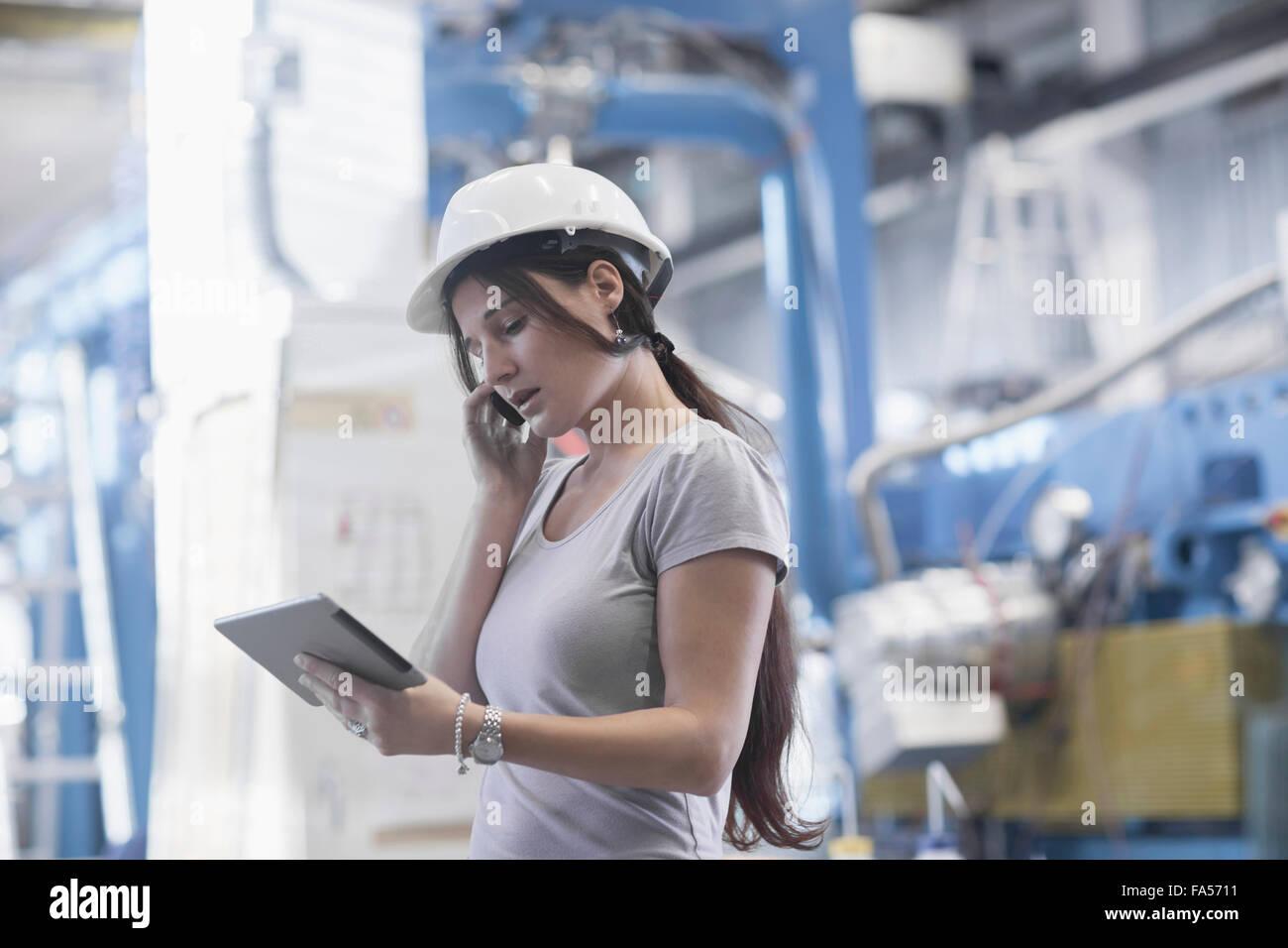 Ingénieur femelle à l'aide d'une tablette numérique et le téléphone mobile dans une installation industrielle, Bade-Wurtemberg, Allemagne Banque D'Images