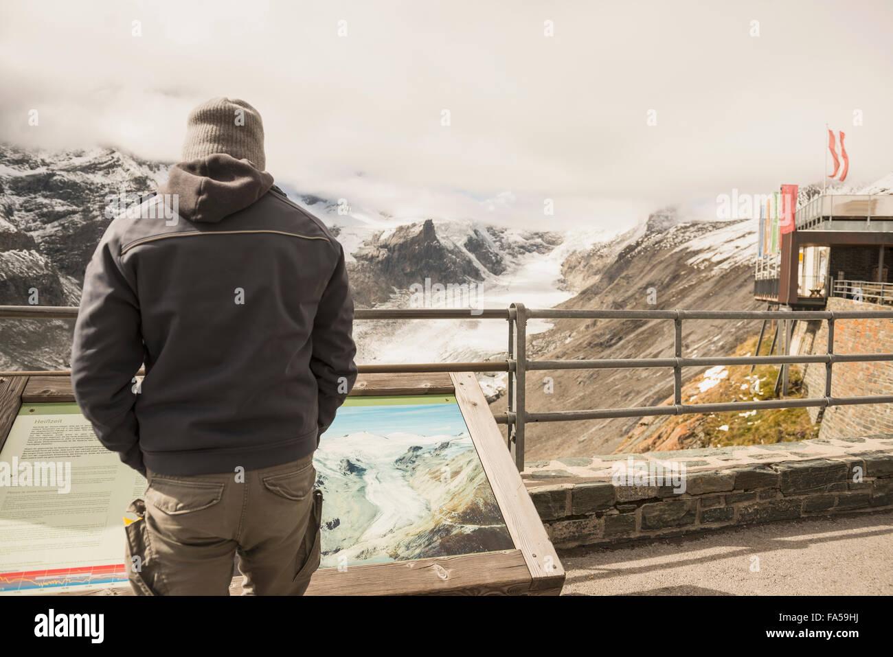 Homme mûr comparant la fonte du glacier du Grossglockner et flux avec un ancien de l'image dans une vitrine, Photo Stock