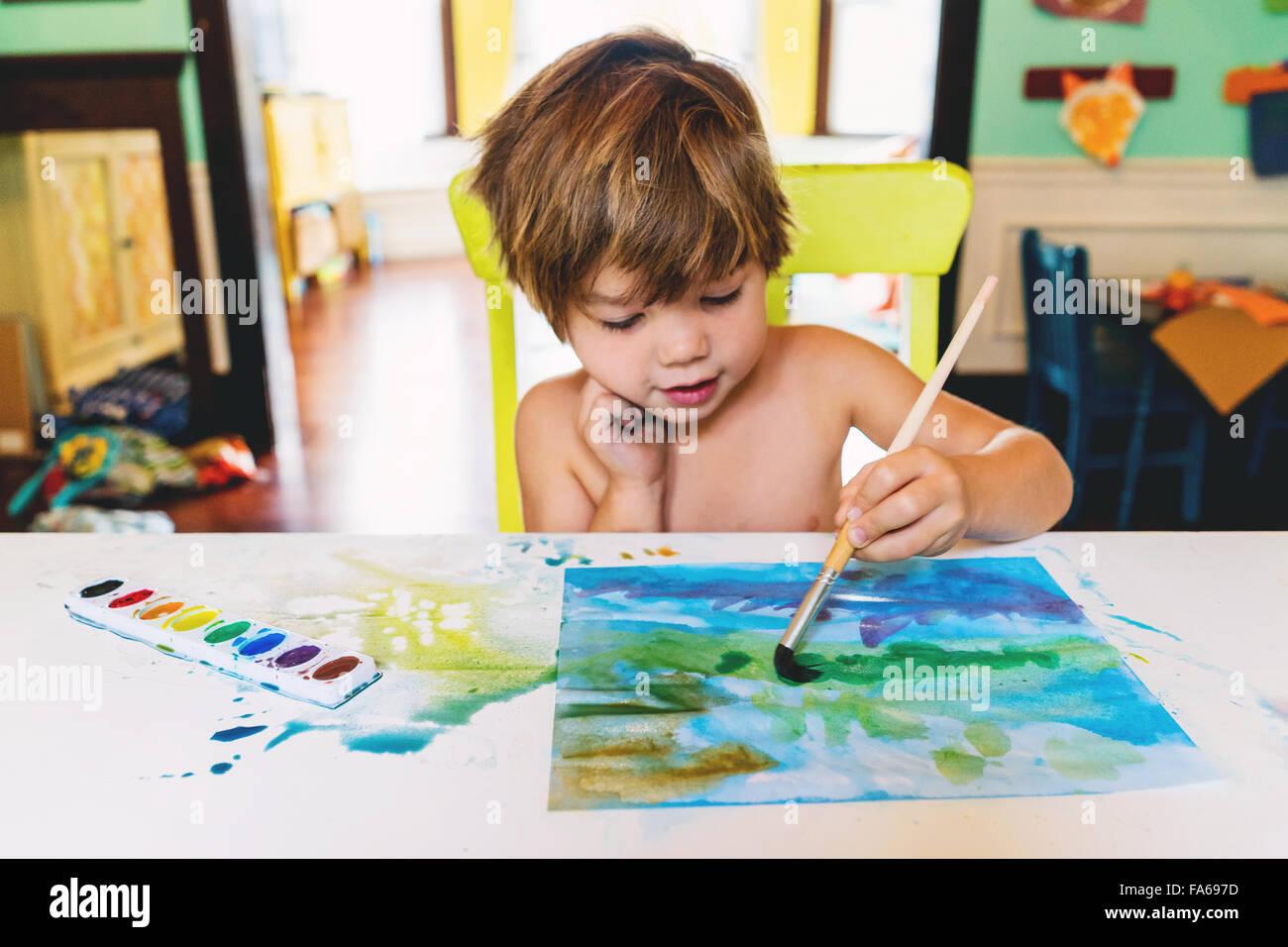 Garçon avec peinture aquarelles Photo Stock