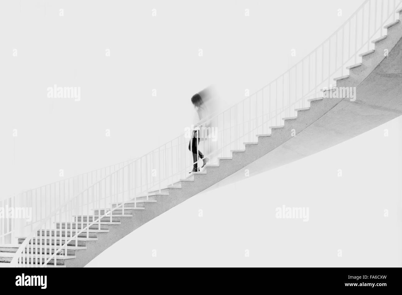 Teenage girl tournant en bas de l'escalier Banque D'Images