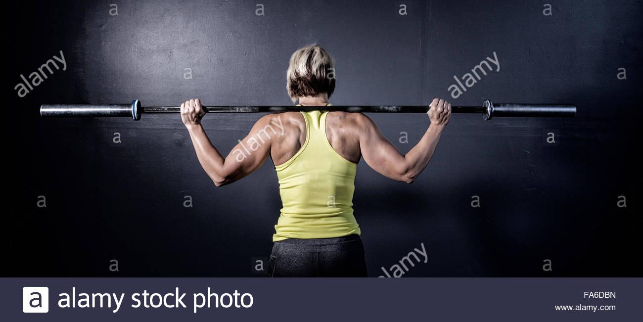 La femme dans un gym Crossfit poids de levage d'un bar Photo Stock