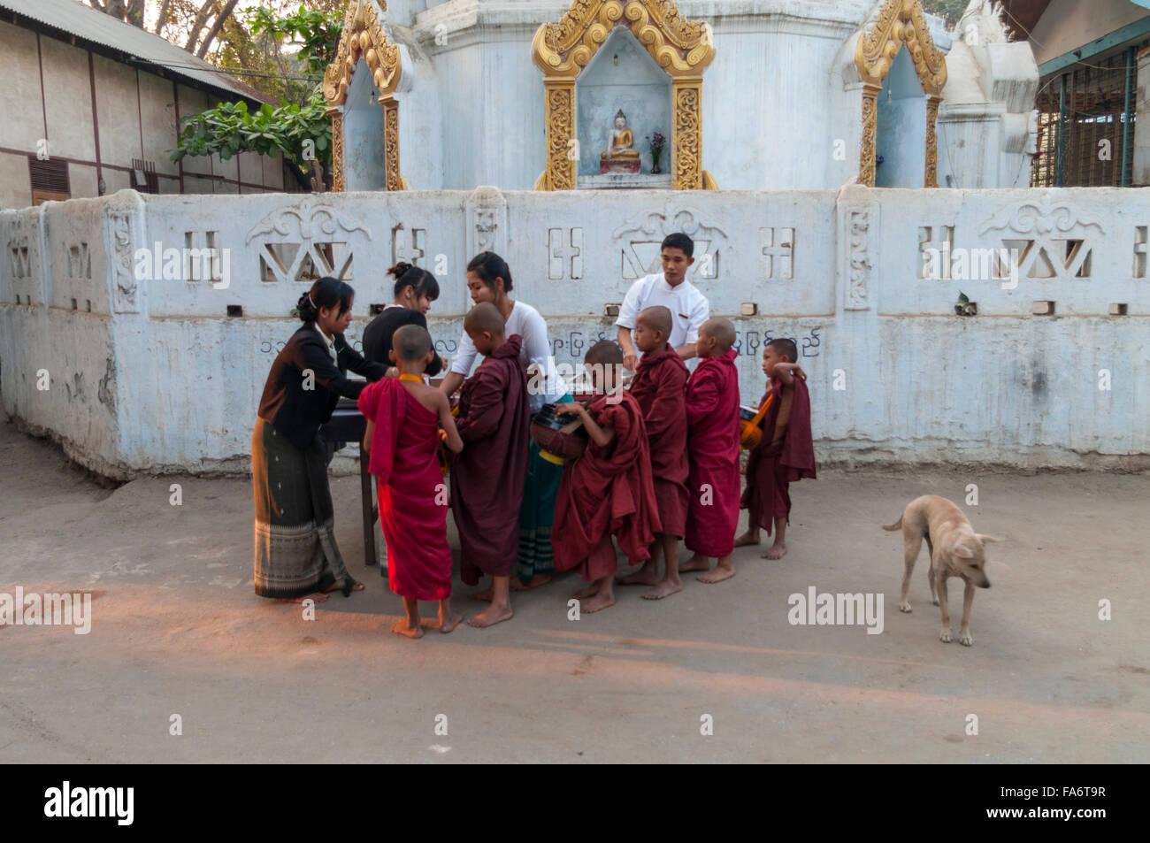 Groupe de jeunes moines bouddhistes recevant des aumônes de l'aumône en ronde Shwe Kyet village encore Photo Stock