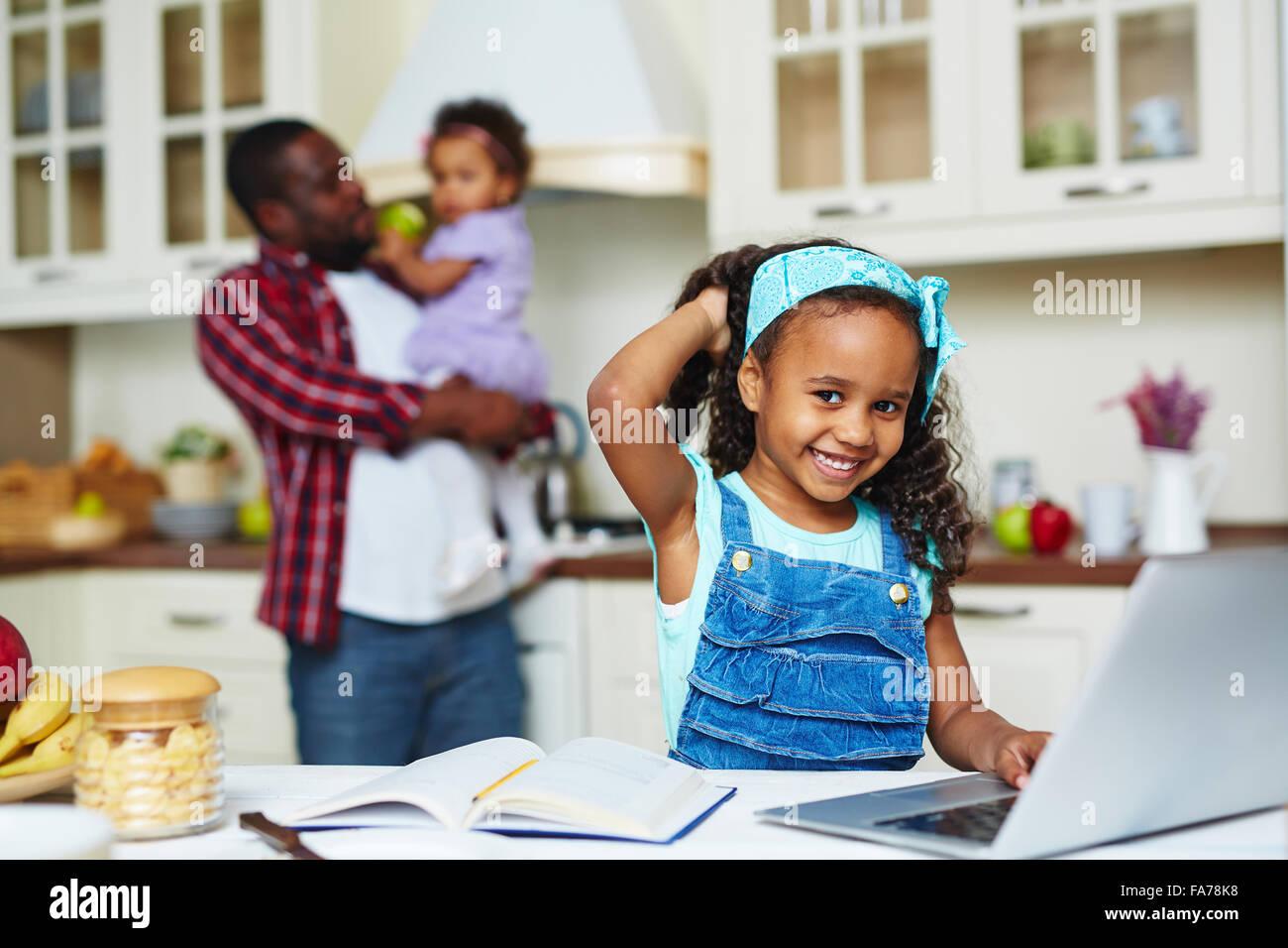 Happy girl looking at camera afro-américain alors que la mise en réseau dans la cuisine Photo Stock