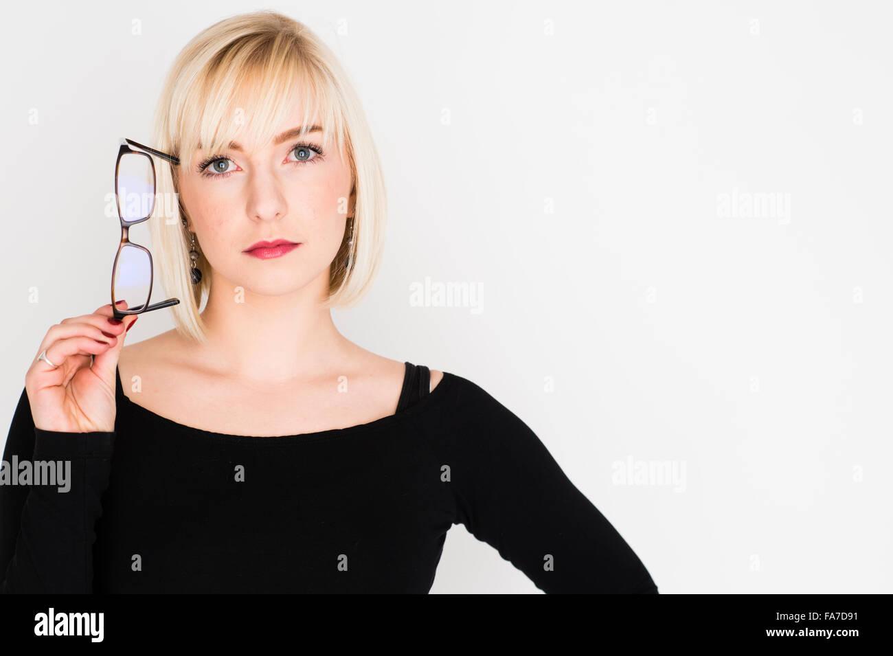 Une jeune femme aux cheveux blonds blonds slim girl, penser, réfléchir, réfléchie, tenant ses Photo Stock