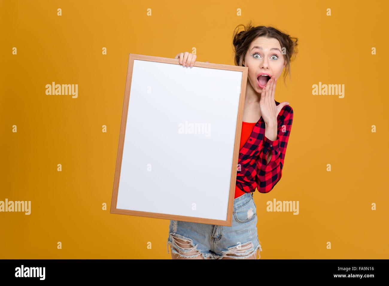 Surpris heureux jeune femme en chemise à carreaux et jeans shorts holding  blank board sur fond 8edec59ee85