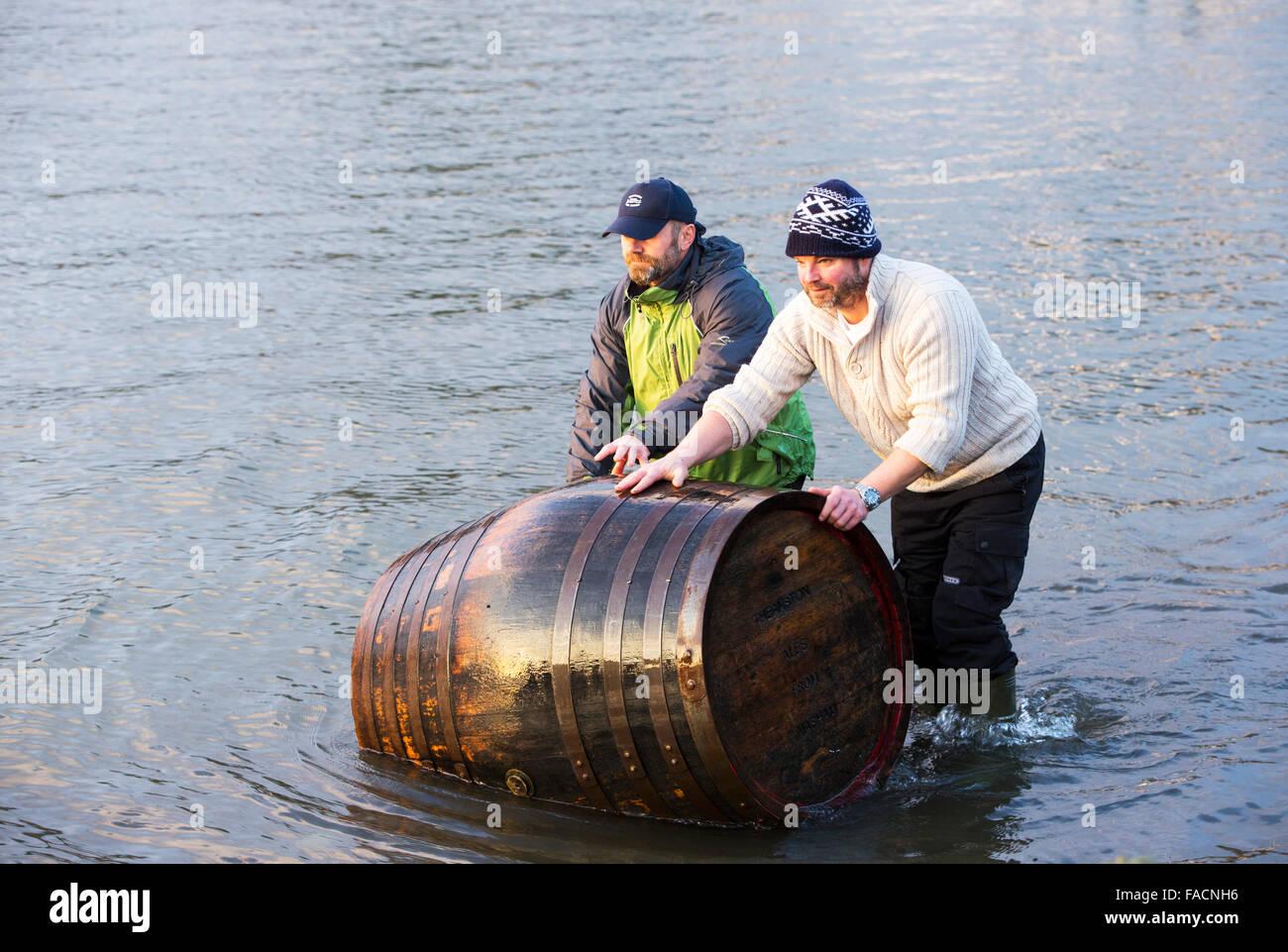 Deux hommes récupérer un baril de bière emportée dans le lac Windermere par les inondations Photo Stock