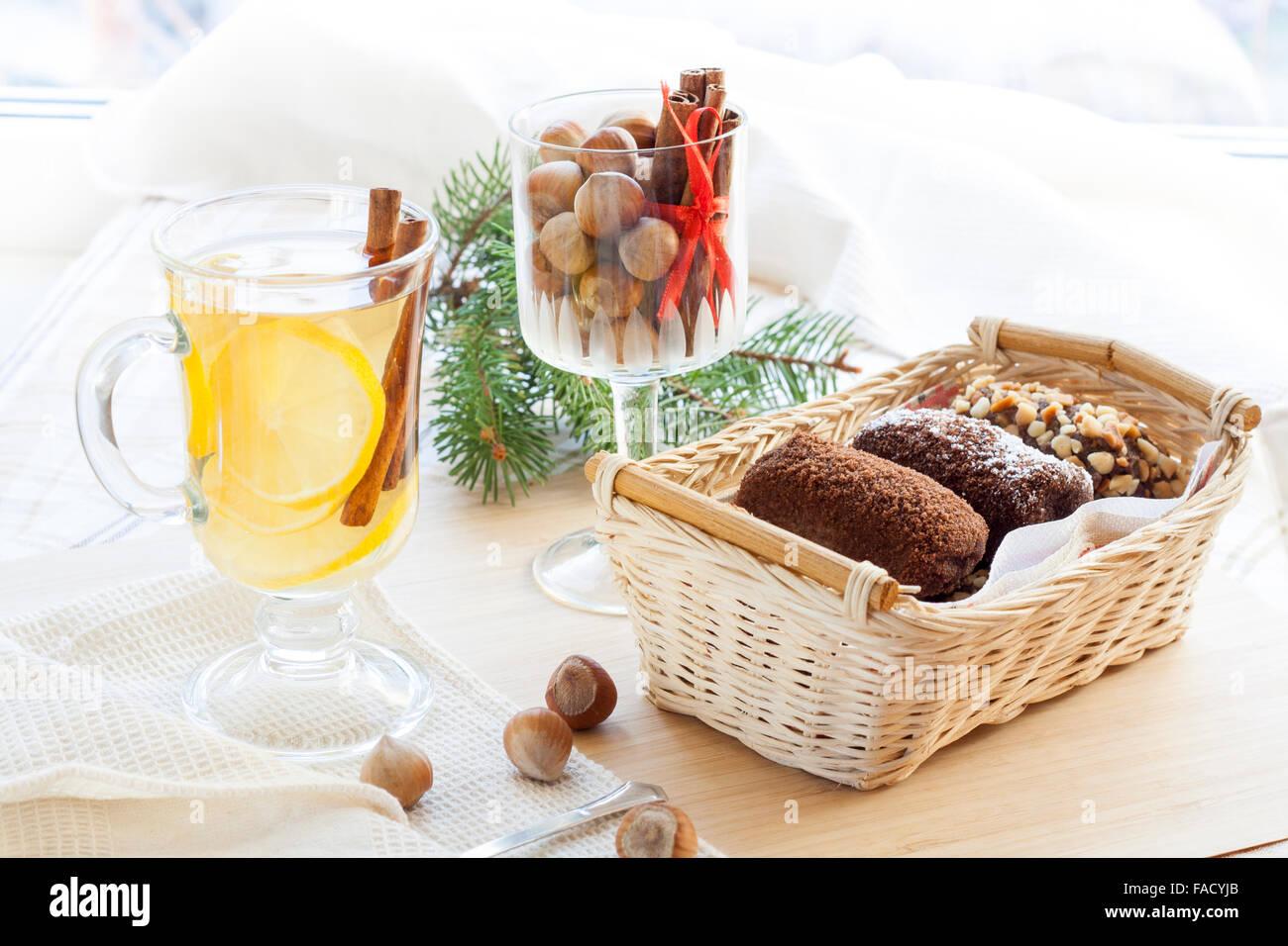 Douce chaude thé vert dans la coupe du verre avec le citron et la cannelle, les gâteaux au chocolat dans le panier Banque D'Images