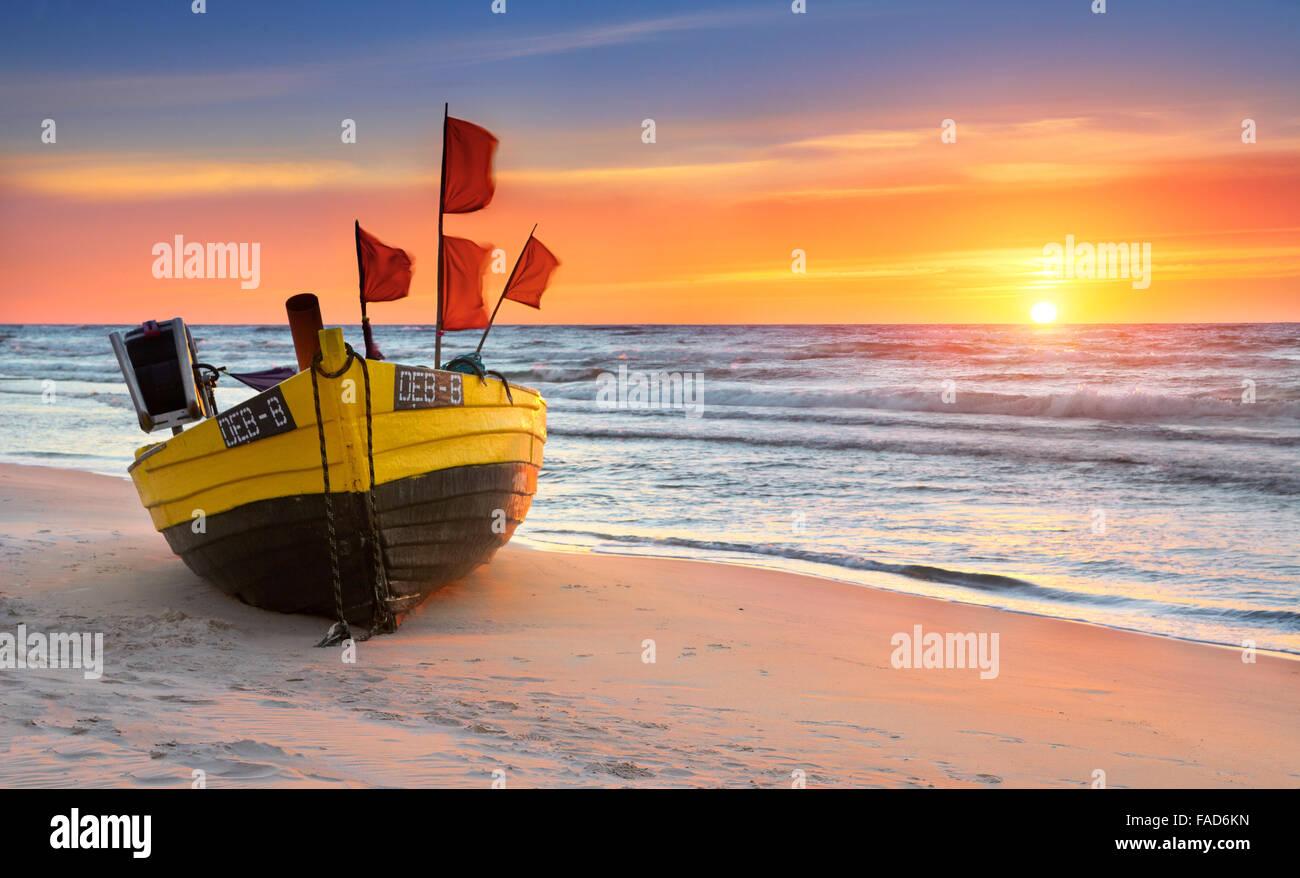 Bateau de pêche sur la plage, à l'heure du coucher du soleil, de la mer Baltique occidentale, Pologne Photo Stock