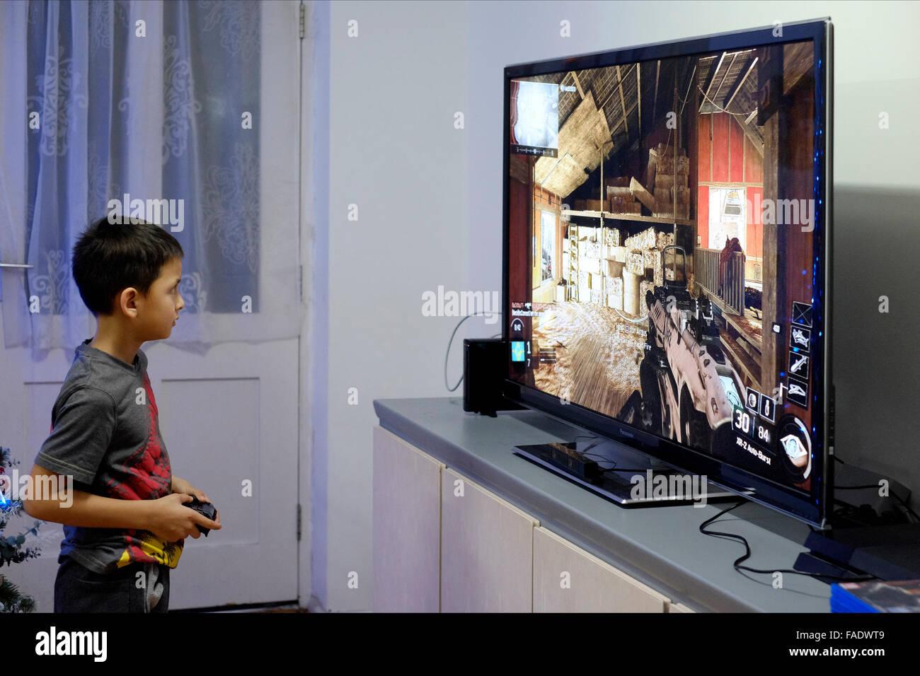 Jeune garçon jouant jeu vidéo sur grand écran plat plat en angleterre Photo Stock