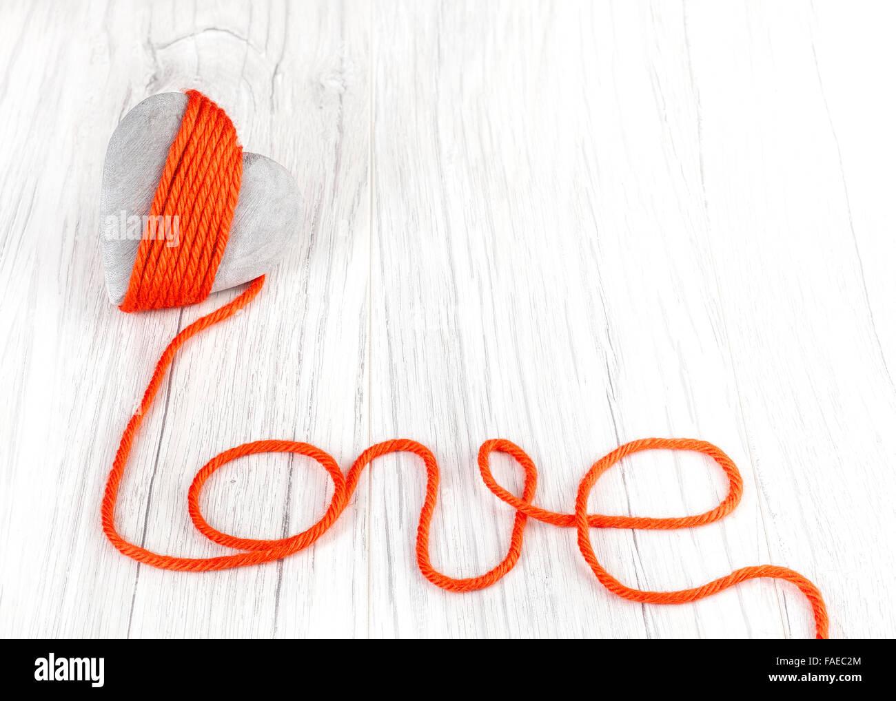 Coeur en bois avec fil rouge signe d'amour, de l'espace pour le texte. Photo Stock