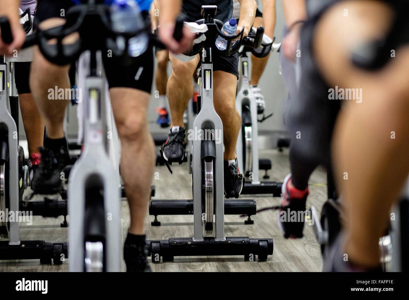 Les bicyclettes stationnaires pendant un cours de gym spinning Photo Stock