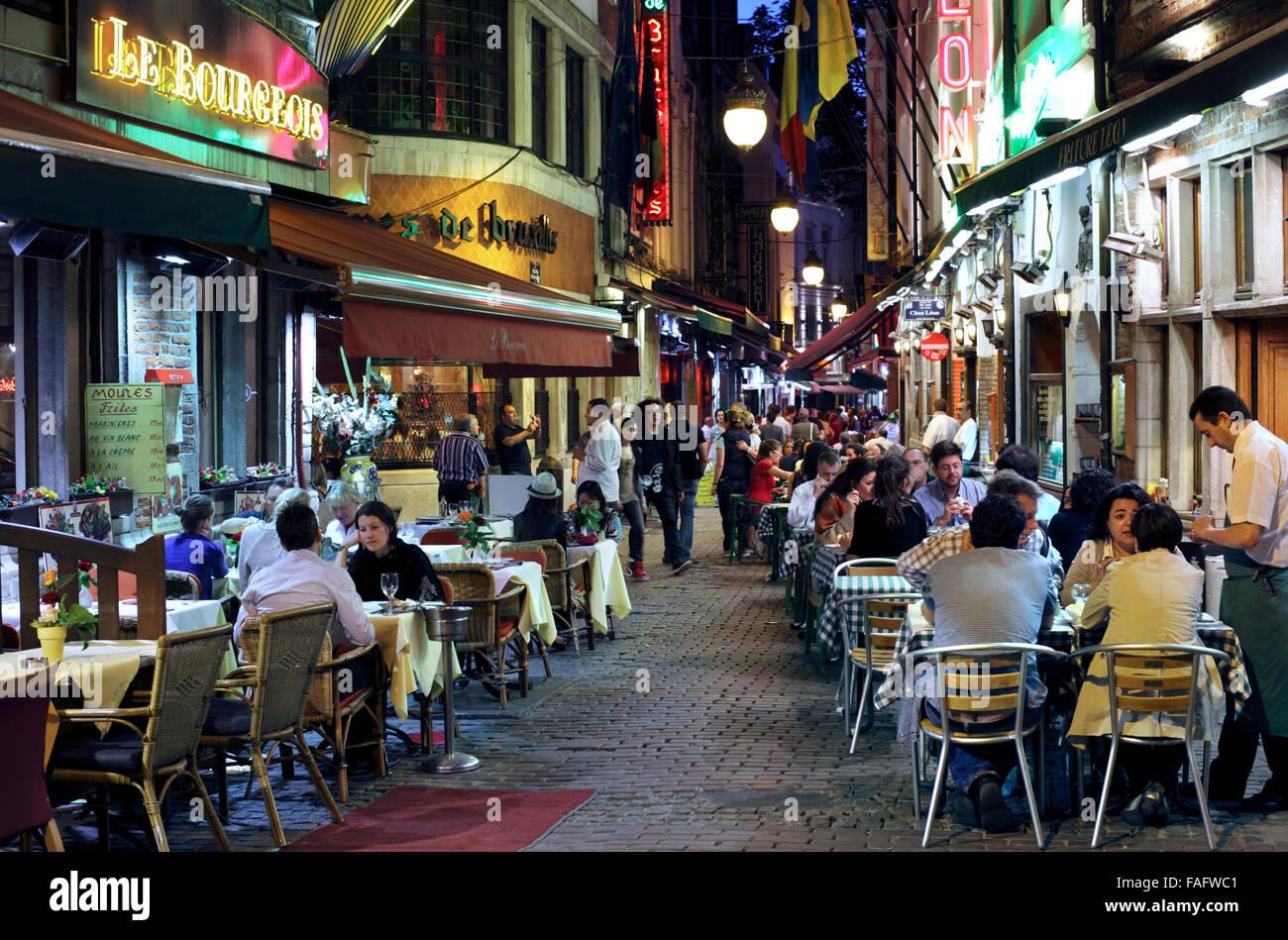 Tables de restaurant débordent sur la chaussée dans la Rue des Bouchers, un piéton retour street Photo Stock