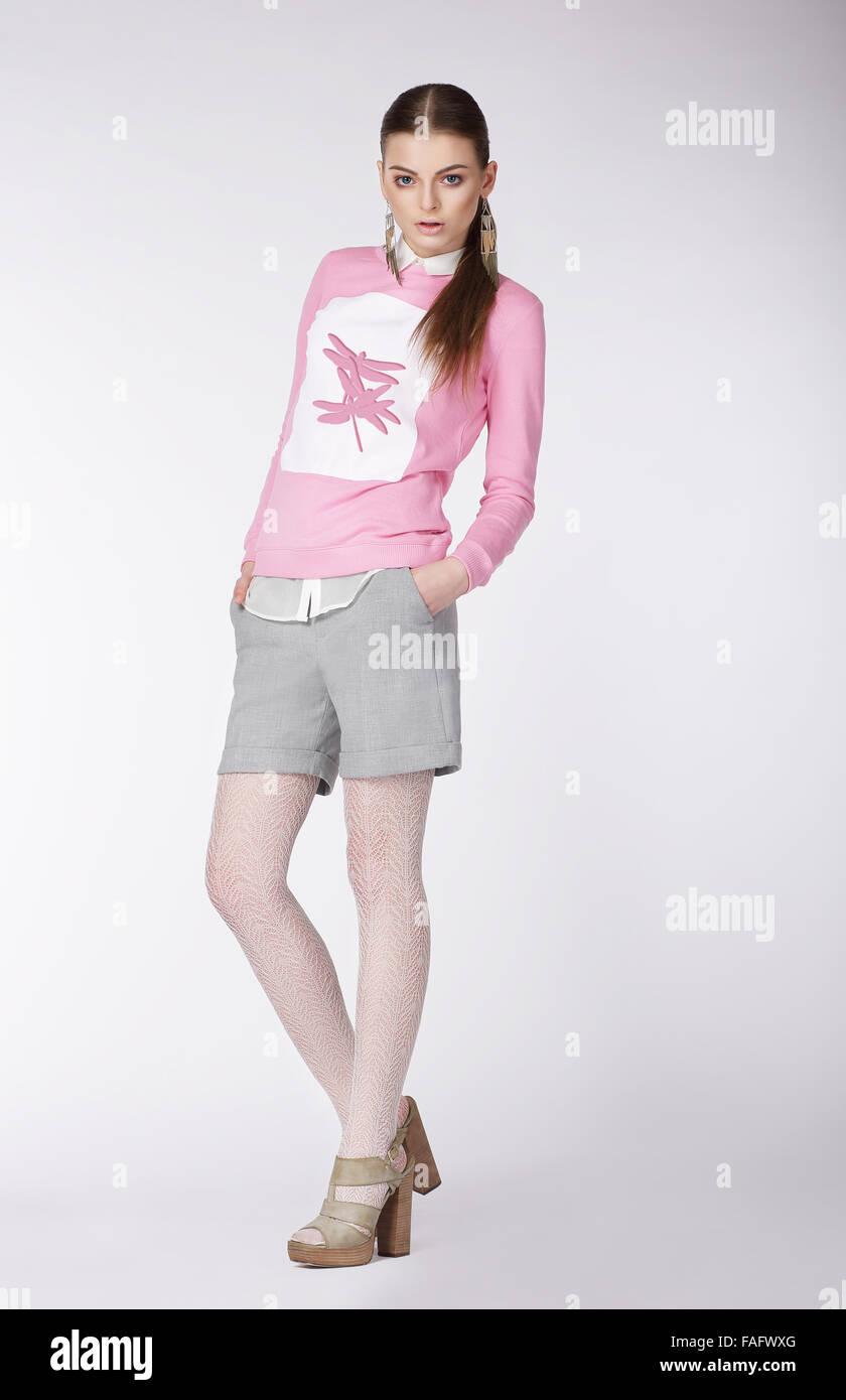 Jeune modèle expressif dans un style décontracté sur fond gris. Photo Stock