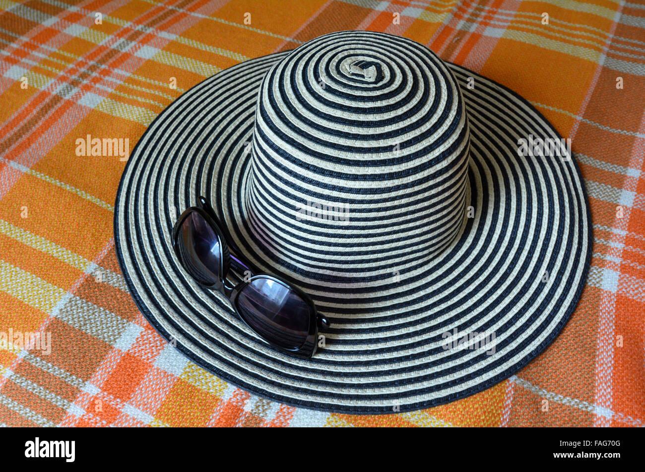 Femme chapeau avec lunettes de soleil sur un lit. Voyage Vacances concept with copy space Photo Stock