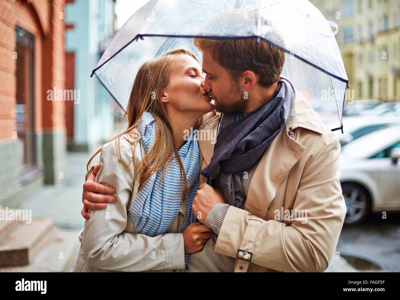 Jeune couple amoureux partager tendre baiser under umbrella Photo Stock