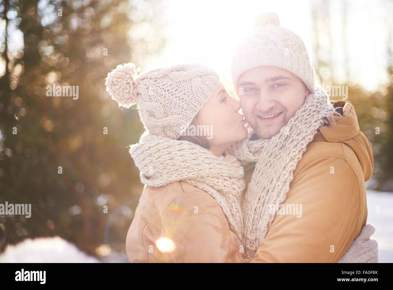 Jeune femme donnant son mari tendre baiser Photo Stock