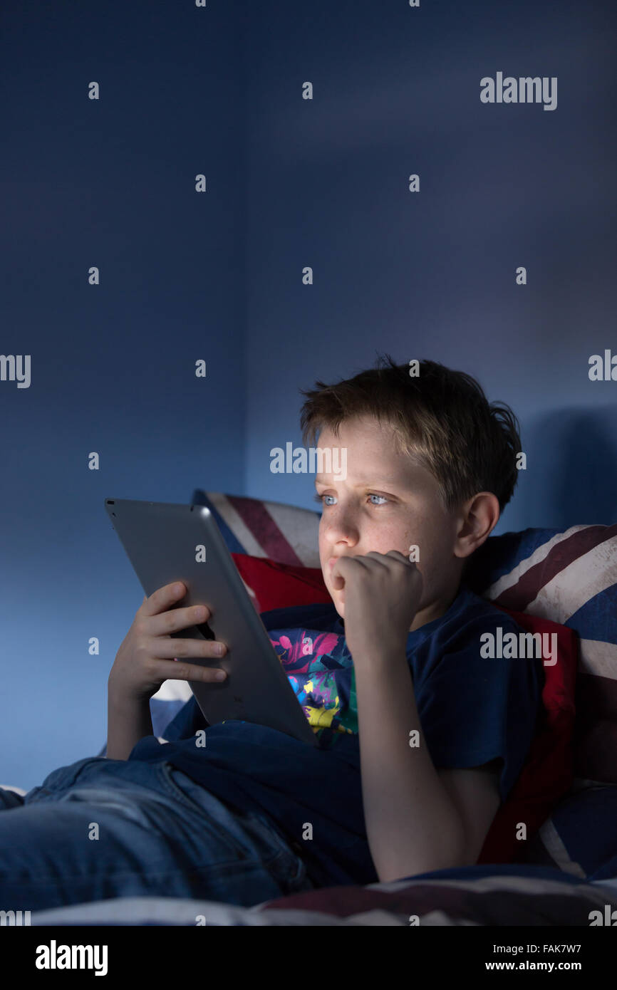 Un garçon assis jusqu'à la fin de sa chambre à la recherche sur l'internet choqué par Photo Stock