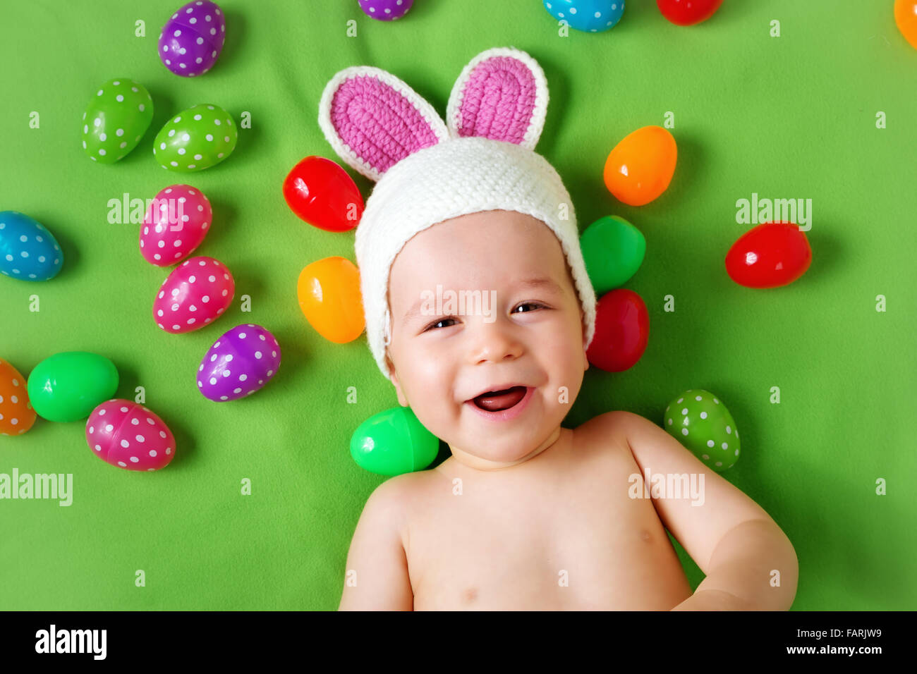Baby Boy in bunny hat lying on blanket vert avec des oeufs de pâques Photo Stock