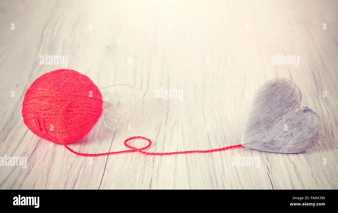 Coeur en bois relié au fil rouge, concept photo. Photo Stock
