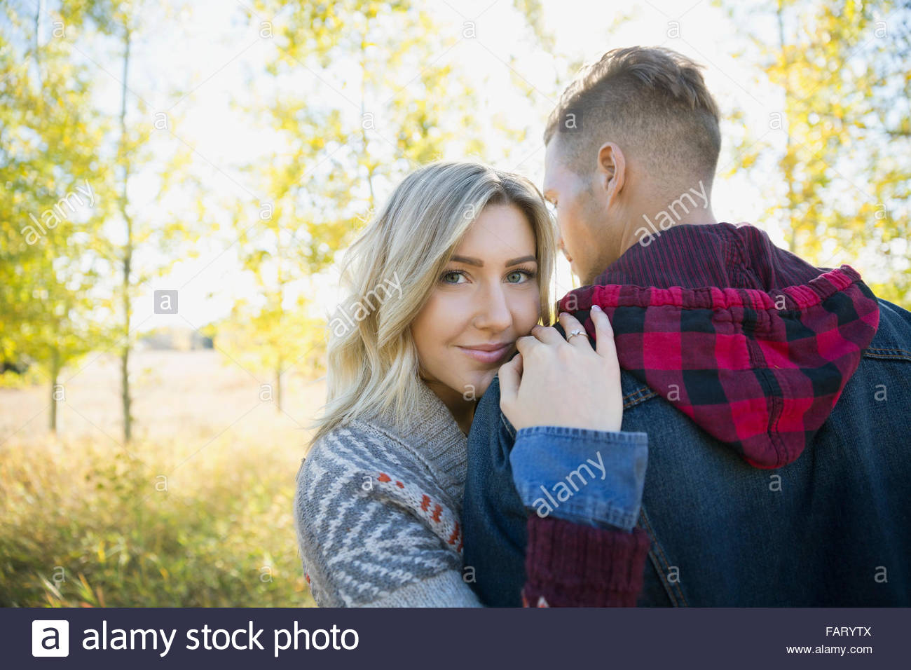 Portrait of smiling woman hugging boyfriend in field Photo Stock