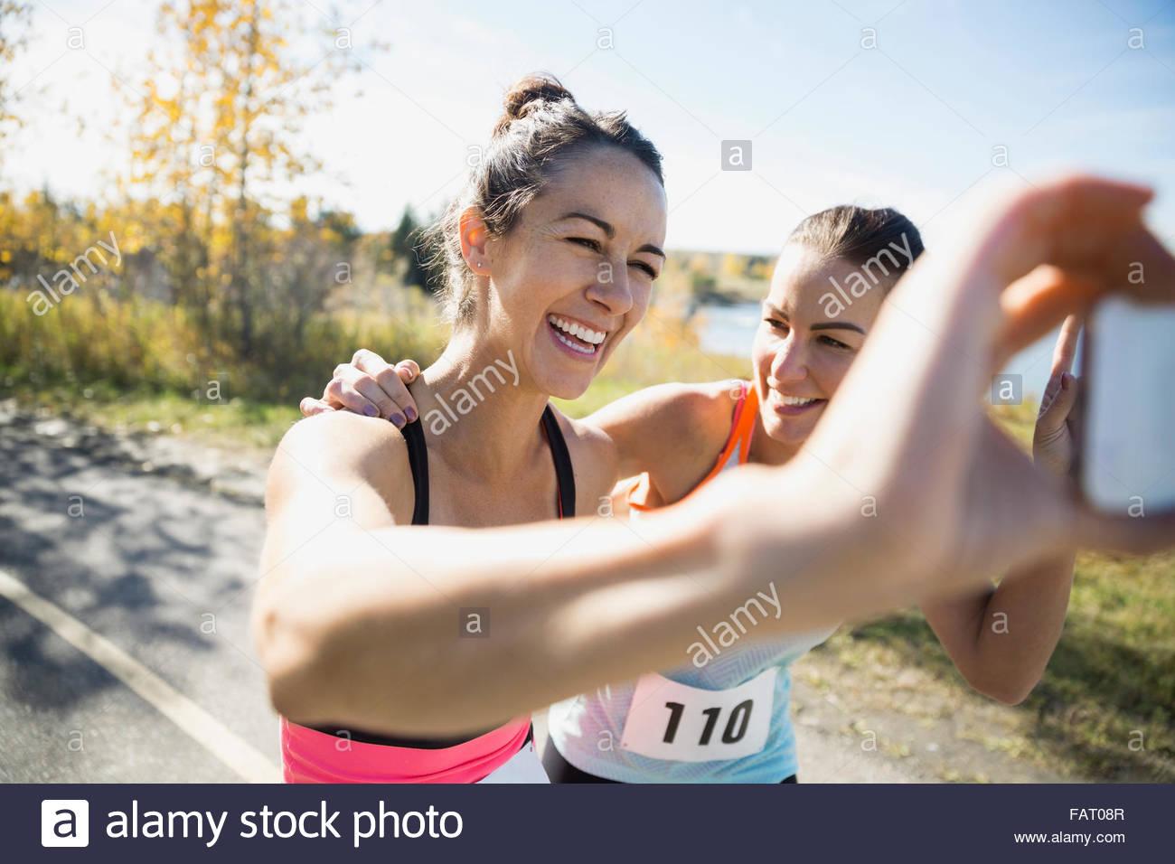 Porteur de rire en tenant le chemin ensoleillé selfies Photo Stock