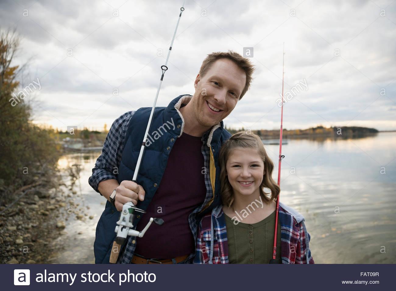 Portrait smiling père et fille de cannes à pêche lakeside Photo Stock